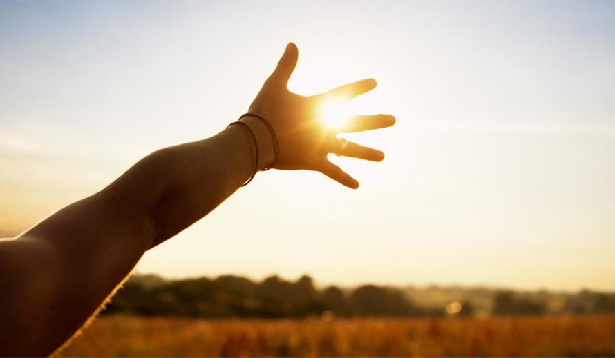 Young woman reaching hand towards sun
